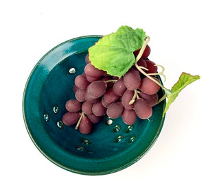 Berry colander in teal glaze on red clay. shown with rinsed  grapes