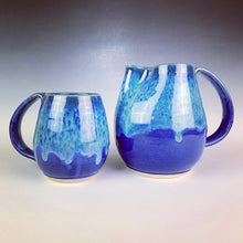 Load image into Gallery viewer, Blue world mug, northwest style coffee mug thrown pottery, with large pulled handle. shown here with matching pitcher