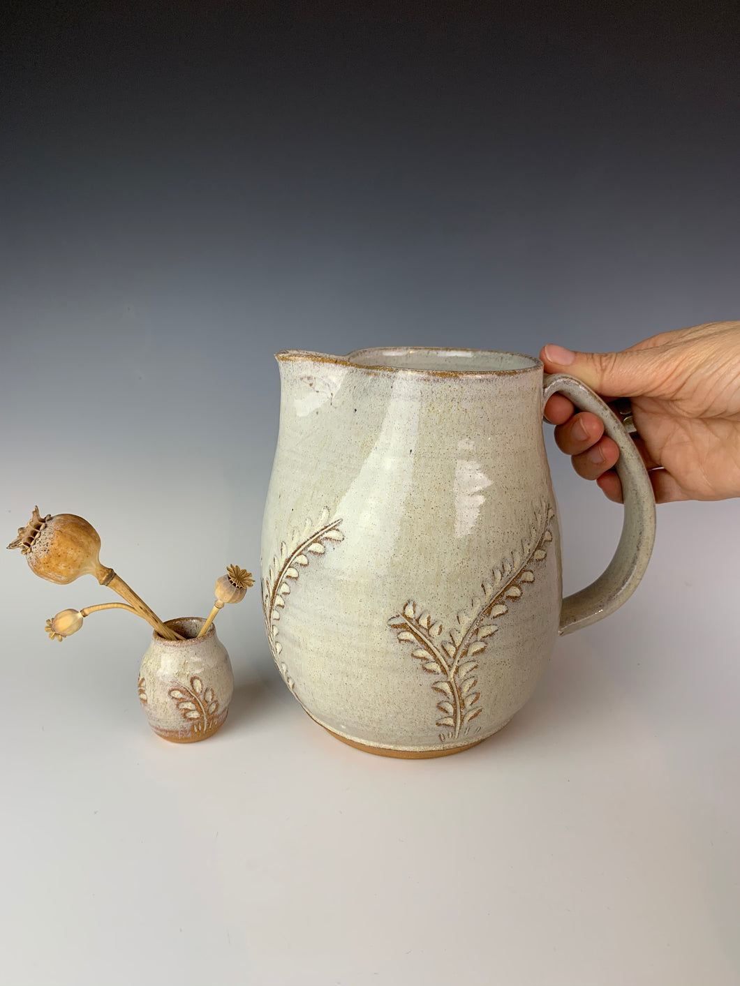 Carved pitcher in speckled white. the red clay and speckled white glaze work well together to show the carved detail. the carved pattern on the vase is reminiscent of vines or growing plants. shown here with a carved bud vase