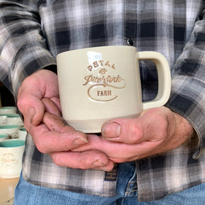 a customized logo stamped into a mug, and inset with brown on white clay.