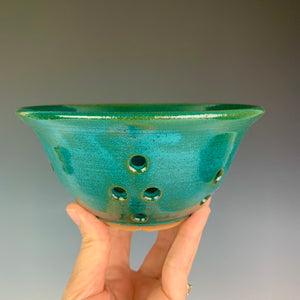 Berry colander in teal glaze on red clay. shown being held by the artist for scale. holds a pint to a pint and a half