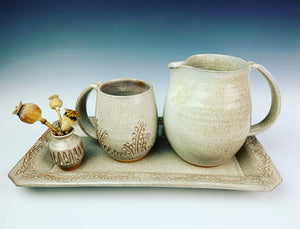 "serving platter (14"" x 9.5"") in carved, speckled white, shown with  matching mug, pitcher and bud vase"