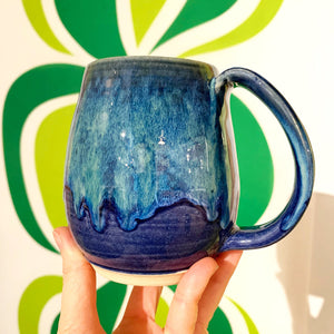 Blue world mug, northwest style coffee mug thrown pottery, with large pulled handle. shown held by the artist