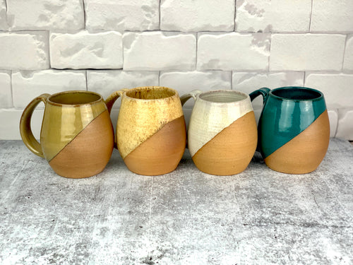 Angle dipped mugs in a variety of colors. These mugs are thrown on the potterys wheel by meredith at Fern Street Pottery.  each one has a pulled handle and is glazed in a dipped pattern that shows the natural clay body in contrast to the smooth glaze.