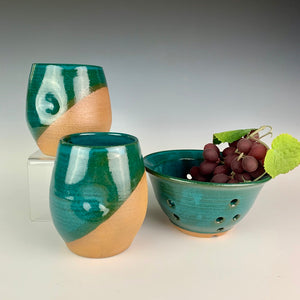 Stemless wine glasses. wheel thrown pottery with finger divots for grip. Jade green glaze over red stoneware clay, glazed at an angle to reveal the clay. shown with berry colander and grapes in teal