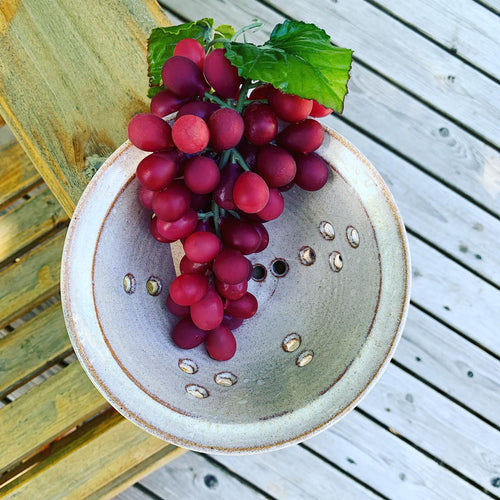 berry colander in speckeld white glaze, shown with grapes. photo taken on an adirondack chair on the deck