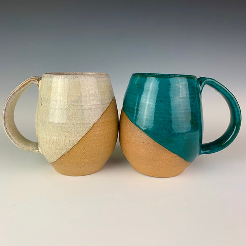 Angle patterned glaze on Hand crafted, wheel thrown pottery mugs. made on the potters wheel in red stoneware clay, glazed in speckled white or teal green glossy glaze. mugs have a pulled handle that fits full finger grip for most, with thumb groove