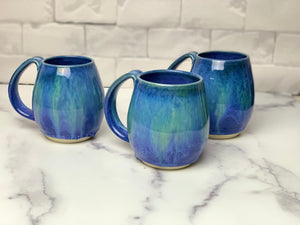 Blue World mugs, blue glaze with melty turquoise blue and green glaze. each one is different. northwest style coffee mug thrown pottery, with large pulled handle.
