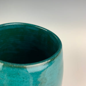 Closeup of Teal Glaze, Angle patterned glaze on Hand crafted, wheel thrown pottery mugs. made on the potters wheel in red stoneware clay, glazed in speckled white or teal green glossy glaze. mugs have a pulled handle that fits full finger grip for most, with thumb groove