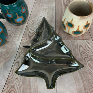 vintage style christmas tree shaped candy dish in Hematite, a chrome-like glaze, shown with midcentury style mugs.