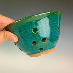 Berry colander in teal glaze on red clay. note the holes for drainage in the sides and the foot of the pot. shown being held by the artist for scale. holds a pint to a pint and a half