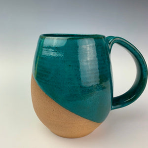 Angle patterned glaze on Hand crafted, wheel thrown pottery mugs. made on the potters wheel in red stoneware clay, glazed in teal green glossy glaze. mugs have a pulled handle that fits full finger grip for most, with thumb groove