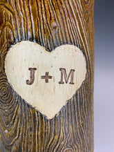 Load image into Gallery viewer, closeup of wood grain textured vase, appears like a tree thrunk with a heart caved into it and initials carved into the heart.