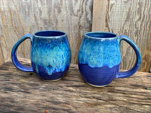 two blue world mugs. no two are alike, the glaze melts and plays differently on each mug