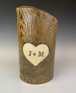 wood grain textured vase, appears like a tree thrunk with a heart caved into it and initials carved into the heart.