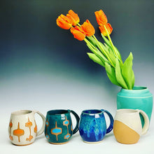 Load image into Gallery viewer, Other mugs available from Fern Street Pottery in the northwest shape. shown here in angle dipped glaze pattern, and MidMod patterns. Also shown with vase in teal