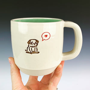 Pug mug for the pug lover. white cylindrical  mug with a pug stamped in in brown, and a heart in a speech bubble in red. Turquoise green interior on this mug.