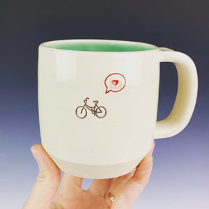 Bike love mug for the bicycle lover. white cylindrical mug with a pug stamped in in brown, and a heart in a speech bubble in red. Turquoise green interior on this mug.