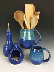 Blue world mug and pitcher, being used as a utensil holder. shown with cobalt blue salt cellar and oil cruet.