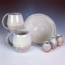 "Load image into Gallery viewer, 7"" stoneware bowl shown with matching mugs tiny bud-vases. all are thrown in a red clay then hand carved, and glazed with a white glaze."