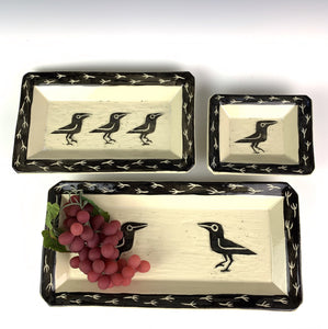 Three  rectangular pottery  trays or serving platters. white stoneware clay with Sgraffito crows or ravens carved in the center, and crow footprints carved around the edges. Shown with grapes