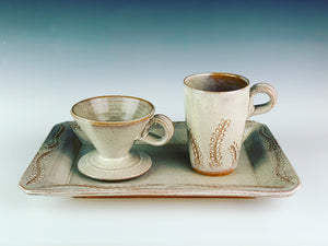 "serving platter (14"" x 9.5"") in carved, speckled white, shown with  matching travel mug and coffee pour over"
