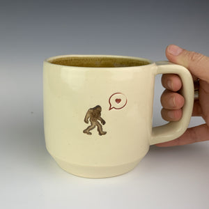 artist holding handle of sasquatch mug. wheel thrown mug