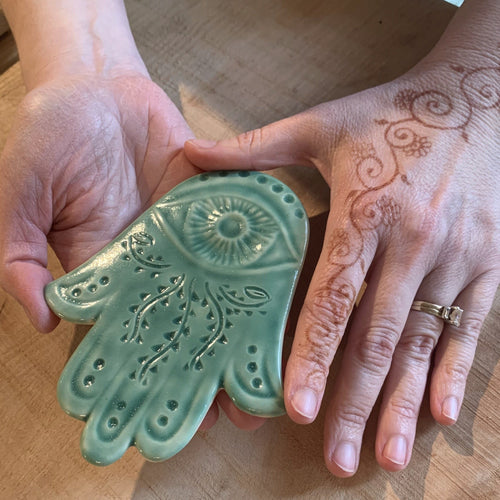 The artist holding a celadon green Hamsa Wall hanging which has been hand carved with a vine pattern. Her hands are also decorated in a vine pattern with Henna.