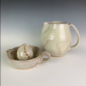 Pottery Citrus juicer, thrown on the wheel in red clay, glazed in speckled white. shown with matching pitcher with carved detail.