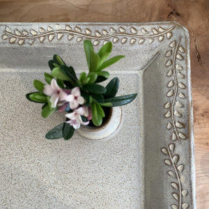 showing the detailed carved edge on a speckled white tray. vine and leaf pattern carved into edge of tray. shown with small matching  bud vase
