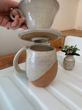 Load image into Gallery viewer, Detail shot of bottom of Coffee pour over and drip edge. wheel-thrown pottery, white glaze with speckled white glaze. shown with matching angle dipped mug and carved bud vase.