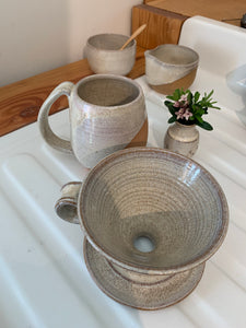 showing the inside of a pottery coffee pour over. notice the wheel thrown pattern inside the cone shape. also shown in the background: matching mug, cream and sugar set and carved bud vase.