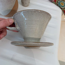 Load image into Gallery viewer, cklesDetail shot of bottom of Coffee pour over and drip edge. wheel-thrown pottery, white glaze with speckled white glaze. shown with matching angle dipped mug in background