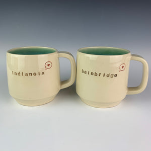 "two cylindrical mugs, wheel thrown, pottery, hand made and with ""bainbridge"" and ""indianola"" pressed into them, and also a cute little image of a heart in a speech bubble."
