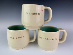 "stack of three indianola mugs. White cylidrical mugs, thrown on the potters wheel. glazed turquoise on the inside. each one is stamped with the word ""indianola"" and another image"
