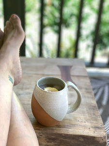 The artist relaxing on her porch with an iced chai and lemon in an angle dipped mug featured in White Speckle. pictured on a handcrafted maple table.