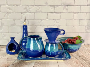 Hand crafted pottery from Fern Street Pottery. Blue world mug, pitcher, tray and colander. Coffee pour over, oil cruet, and salt cellar in cobalt blue.