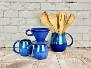 two blue world mugs shown with a blue coffe pour over, and a matching pitcher, used as utensil holder