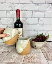 Load image into Gallery viewer, set of pottery wine glasses in speckled white glaze. angle dipped glaze, shown with a matching berry colander.