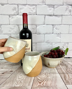 set of pottery wine glasses in speckled white glaze. angle dipped glaze, shown with a matching berry colander.