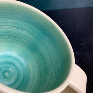 a custom mug shown with standard turquoise glaze inside