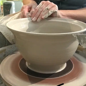 potter throwing a large bowl on the wheel, to be made into a colander.