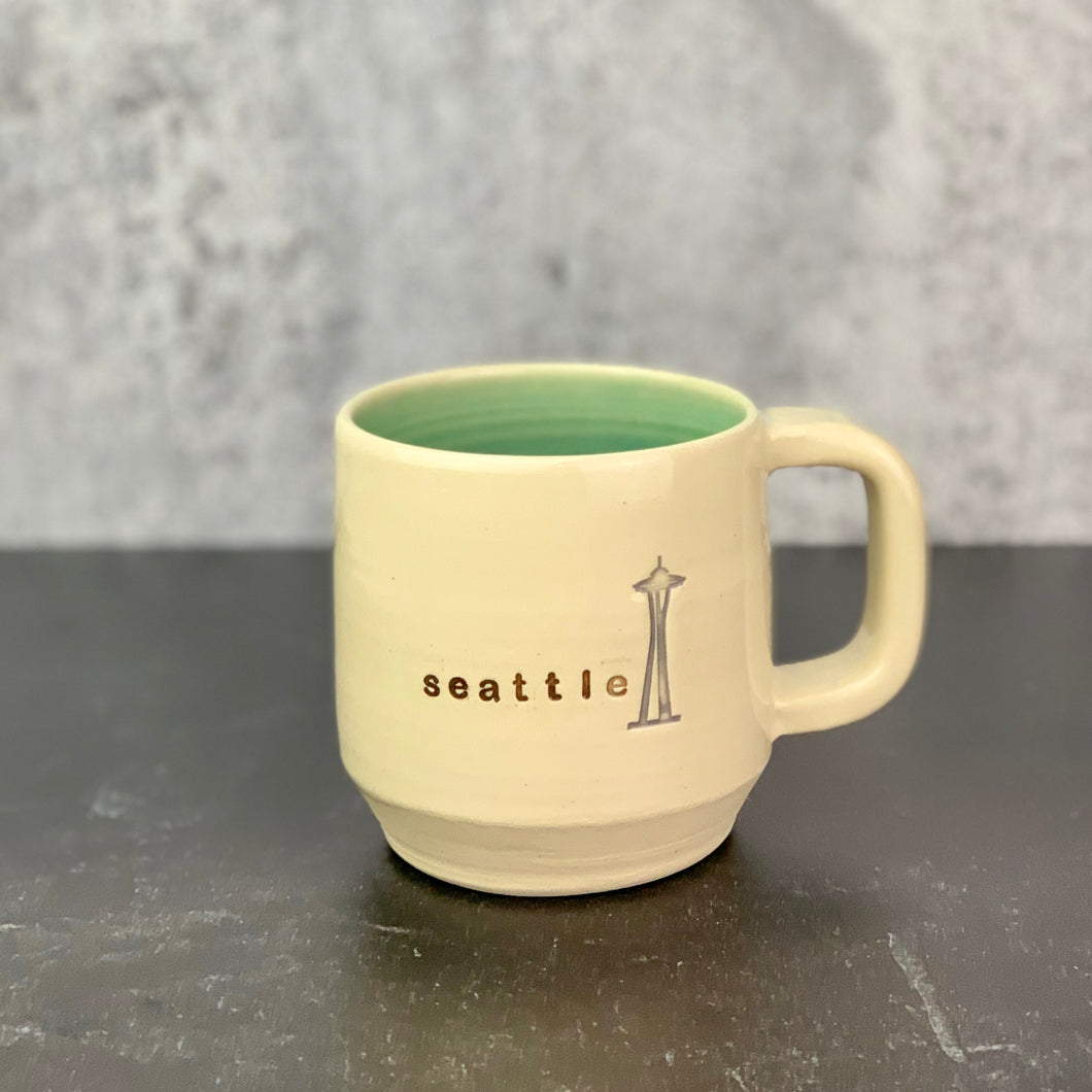 Wheel thrown mug, City Mug with Seattle and an image of the space needle. white clay, turquoise glaze inside.