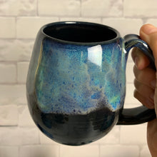Load image into Gallery viewer, Aurora Borealis mug, blue over black glaze, northwest style coffee mug thrown pottery, with large pulled handle. shown held by the artist