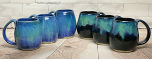 Blue World mugs, and Aurora Borealis Mugs. each one is different. northwest style coffee mug thrown pottery, with large pulled handle.