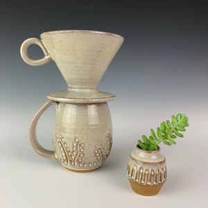 carved bud vase shown with carved mug and coffee pour over in speckled white glaze. all were thrown on the potters wheel by meredith at Fern Street Pottery