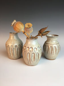 Three different but matching bed vases. tiny pottery vases thrown on the potter's wheel in red clay, carved, then glazed in white. shown with dried flowers