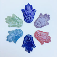 Load image into Gallery viewer, An array of Hamsas in a variety of colors, each one hand carved with an eye and a vine pattern, or a fish pattern. Cobalt Blue, Rose Pink, Lavender Purple, Celadon Green, Skye Blue.