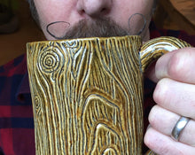 Load image into Gallery viewer, lumberjack style, handlebar mustache, man drinking out of a large pottery mug that is carved to look like tree bark