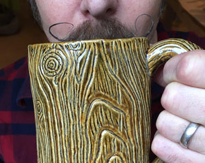 lumberjack style, handlebar mustache, man drinking out of a large pottery mug that is carved to look like tree bark